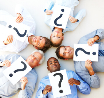 Portrait of a group of business people lying down in a circle while holding a question mark